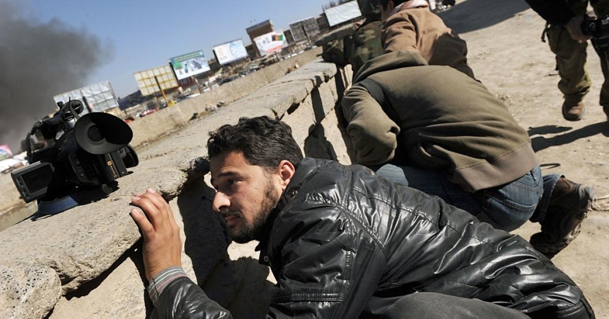 Afghan journalists seek cover in Kabul on Jan. 18, 2010.</p>