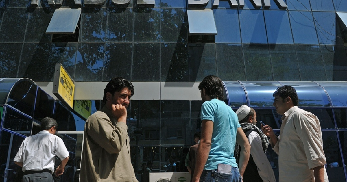 Afghan pedestrians walk past the main branch of The Kabul Bank in Kabul on Sept. 4, 2010.</p>