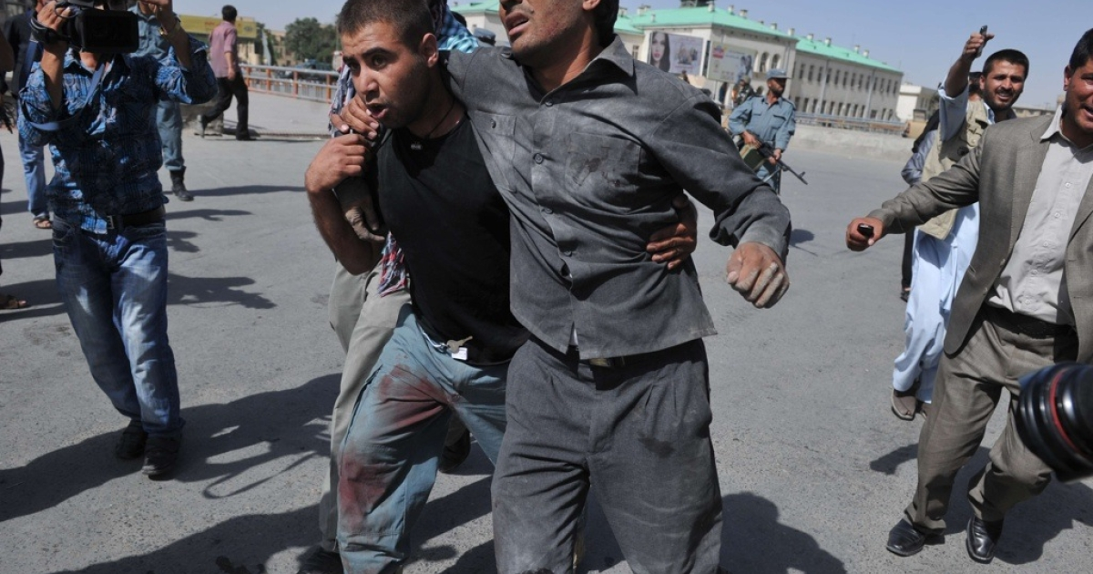 An Afghan policeman helps a wounded man during clashes following an attack on a police station at the main market in central Kabul on June 18, 2011. Armed militants stormed a police station in the heart of the Afghan capital, triggering an explosion and ongoing heavy exchange of fire, officials and witnesses said. The attackers got into the police station in the crowded main central market area, close to the Afghan presidential palace, defence ministry and other official buildings.</p>