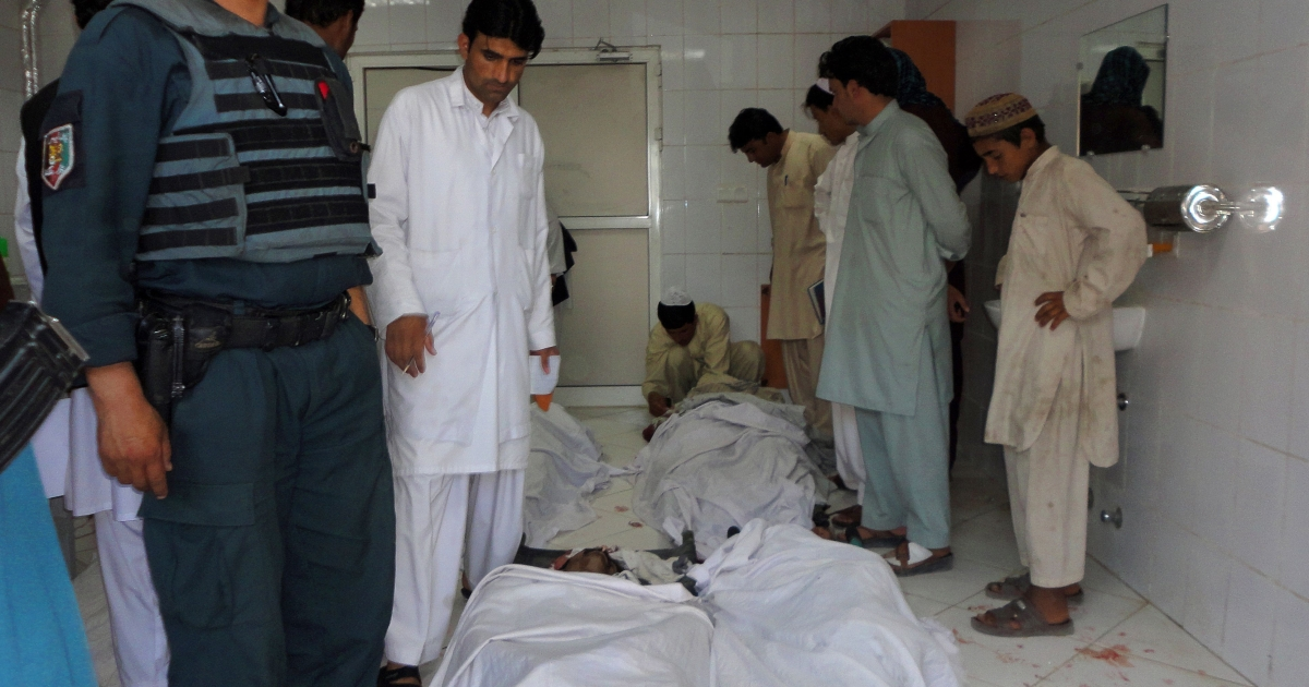 Afghan policeman and civilians gather at a hospital morgue holding the bodies of suicide bombing victims in Khost on June 20, 2012.</p>