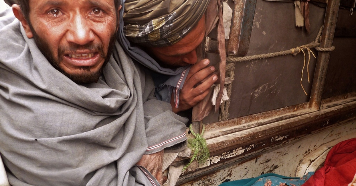 A mourner cries over the bodies of Afghan civilians, allegedly shot by a rogue US soldier, seen loaded into the back of a truck in Alkozai village of Panjwayi district, Kandahar province on March 11, 2012.</p>
