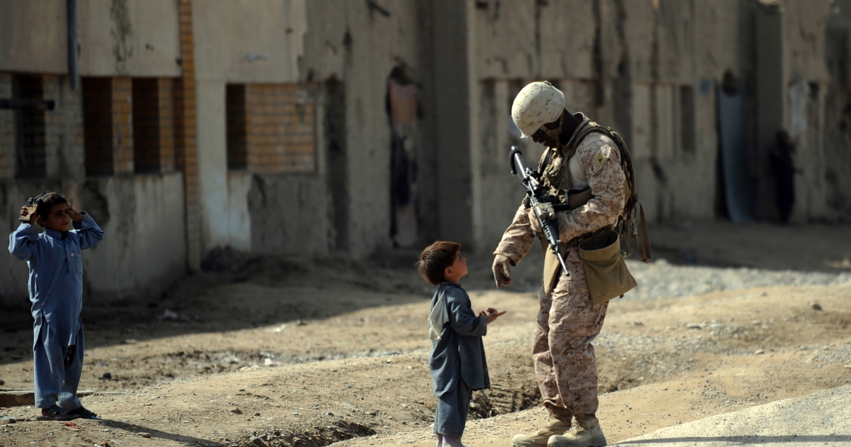 A U.S. Marine from 2nd Batallion, 1st Marines Regiment talks to a child during a patrol in Gamser on Feb. 20, 2011. There are around 140,000 international troops in Afghanistan, two-thirds of them from the United States.</p>
