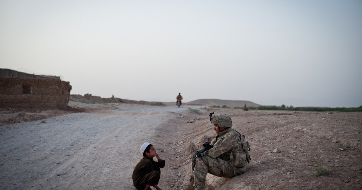 Sgt. Oscar Cuellar and an Afghan boy consider each other for a moment in the outskirts of Qalat, the capital of Zabul Province.</p>