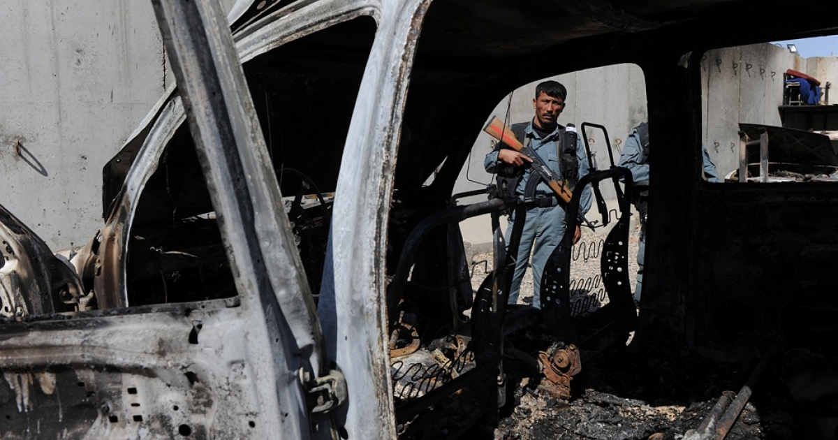 An Afghan policeman stands guard near the charred remains of a vehicle at the UN headquarters after protesters attacked the compound in Mazar-i-Sharif on April 2, 2011.</p>