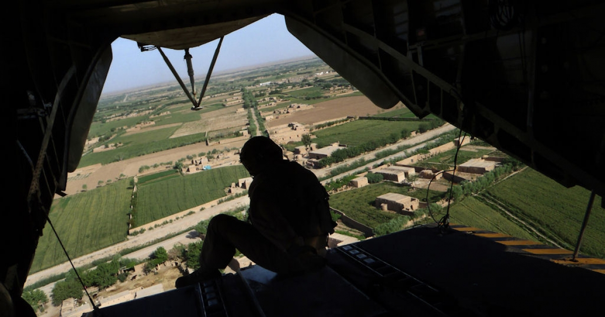 A member of the U.S. Marine helicopter CH 53 crew sits at the back door as it flies over Marjah district in Helmand Province, Afghanistan, on May 3, 2011.</p>
