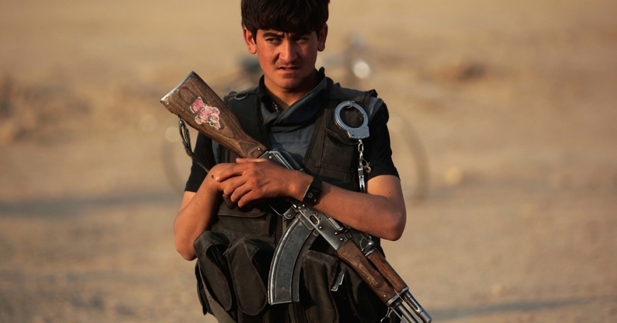 A young member of the Afghan National Police guards the perimeter of a meeting among Afghan Pashtun tribal elders in the Kandahar province of Afghanistan.</p>