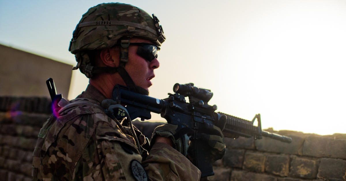 Staff Sgt. Andy Searles, of 202nd Military Police Company, scans a vacant lot in Kandahar City during a patrol on July 13.</p>