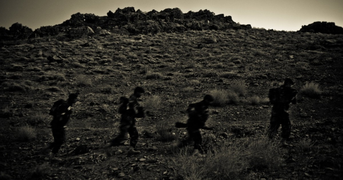 U.S. soldiers march in the cover of night.</p>