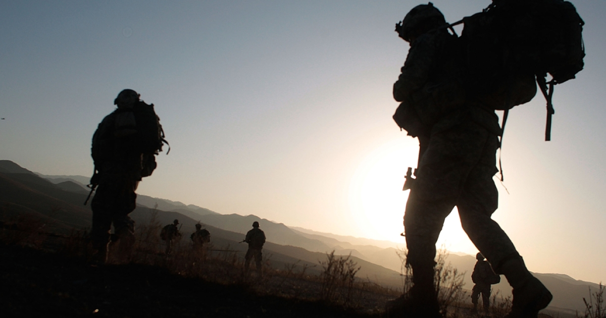 Soldiers of the 1/501st of the 25th Infantry Division begin marching at sunrise after being air-dropped into a field October 14, 2009 in Paktika Province, Afghanistan.</p>