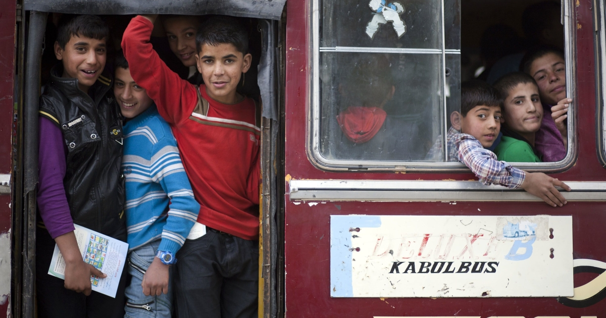 Afghan children ride a bus after taking part in a performance to celebrate the second