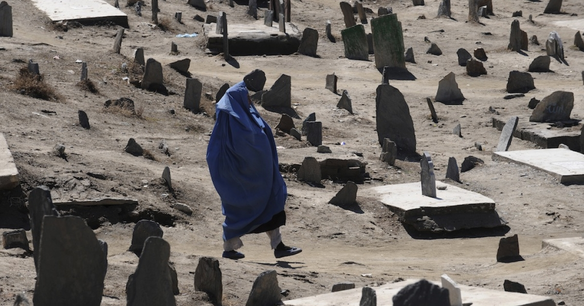 A burqa-clad Afghan woman walks in a Muslim cemetery in Kabul on March 9, 2011.</p>
