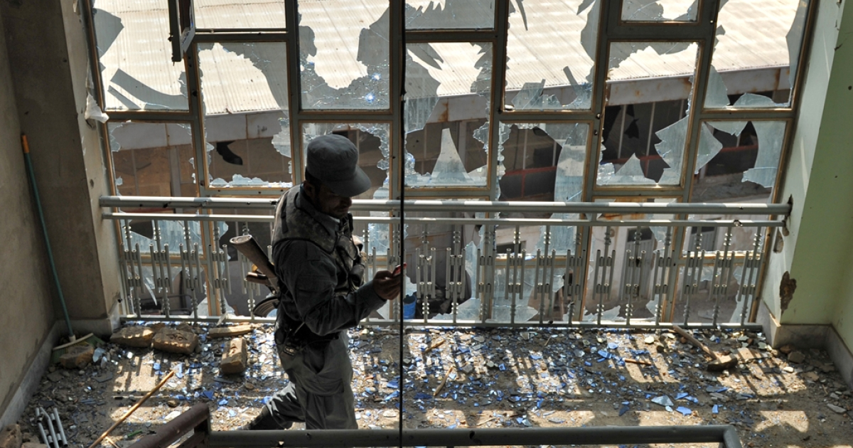 A policeman takes a photo with his mobile phone in the building from which insurgents launched an attack in Kabul on April 16, 2012. Afghanistan said its forces regained control of Kabul on April 16, after killing Taliban militants, some disguised as women in burqas,who launched one of the biggest attacks on the capital in a decade of war.</p>
