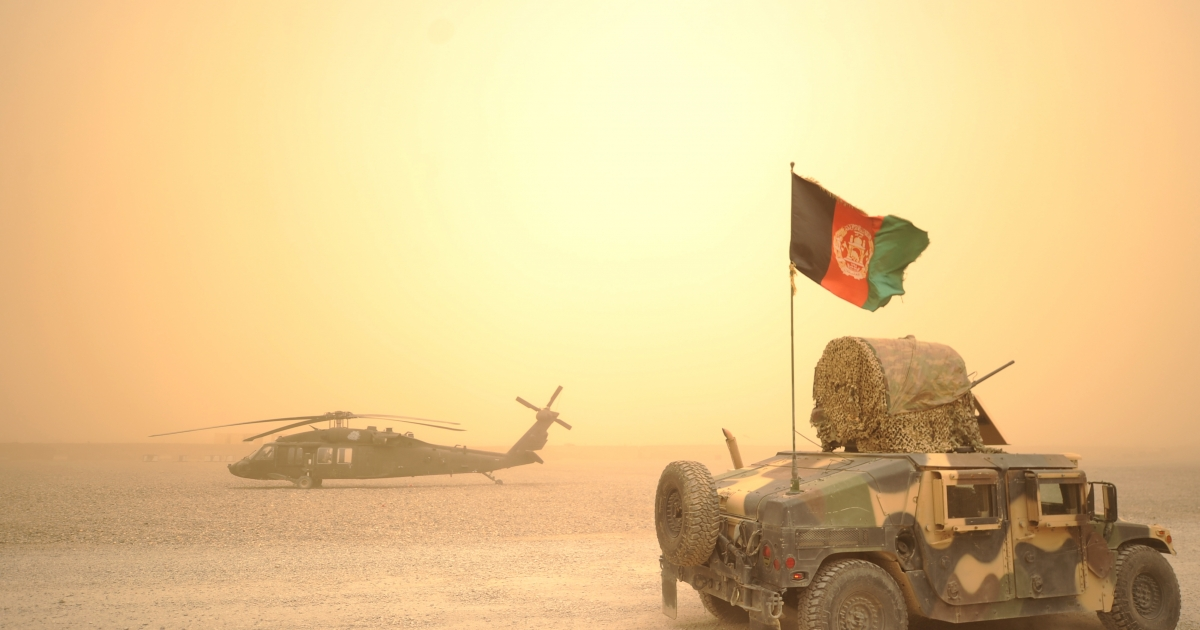 An Afghan National Army Humvee jeep drives past a U.S. army Black Hawk helicopter from Alpha Company 7-101 AVN during a sandstorm at FOB Wilson in Kandahar province in southern Afghanistan on March 27, 2011. Around 140,000 foreign troops are deployed in Afghanistan within the U.N.-mandated, NATO-led, International Security Assistance Force (ISAF) and the US-led coalition Operation Enduring Freedom, which overthrew the Taliban in late 2001.</p>