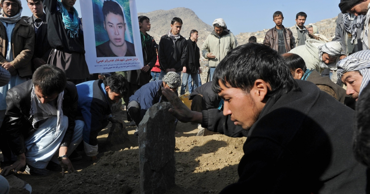 Afghan men bury victims of a bomb attack against Shiite Muslims outside the Karti Sakhi Shrine in Kabul on December 7, 2011.</p>