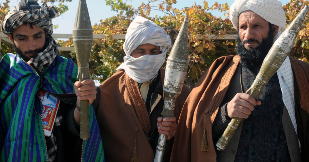 Former Taliban fighters display their weapons after they joined Afghan government forces during a ceremony in Herat on November 3, 2012.</p>