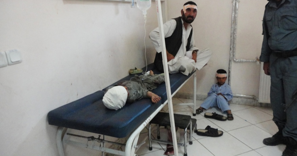 An Afghan policeman looks at a wounded man and children sitting in the main hospital in Khost city on October 1, 2012. A suicide attack on a joint Afghan-NATO foot patrol killed at least 14 people, including three NATO soldiers and an interpreter, officials said. Four Afghan police and six civilians were also killed, and 37 were wounded in the attack near a market in the eastern city of Khost, the provincial governor's office said.</p>