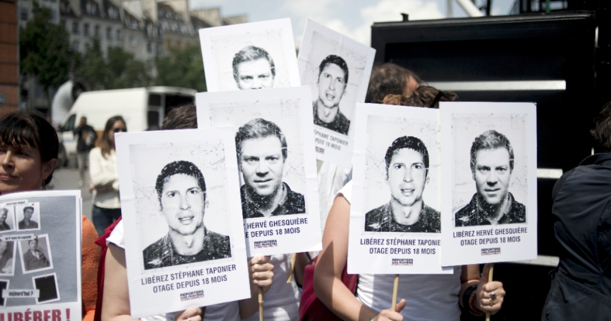 People hold placards with pictures of the two French journalists kidnapped by the Taliban in Afghanistan in December 2009, on June 29, 2011 in Paris, during a demonstration prior to the announcement of their release.</p>