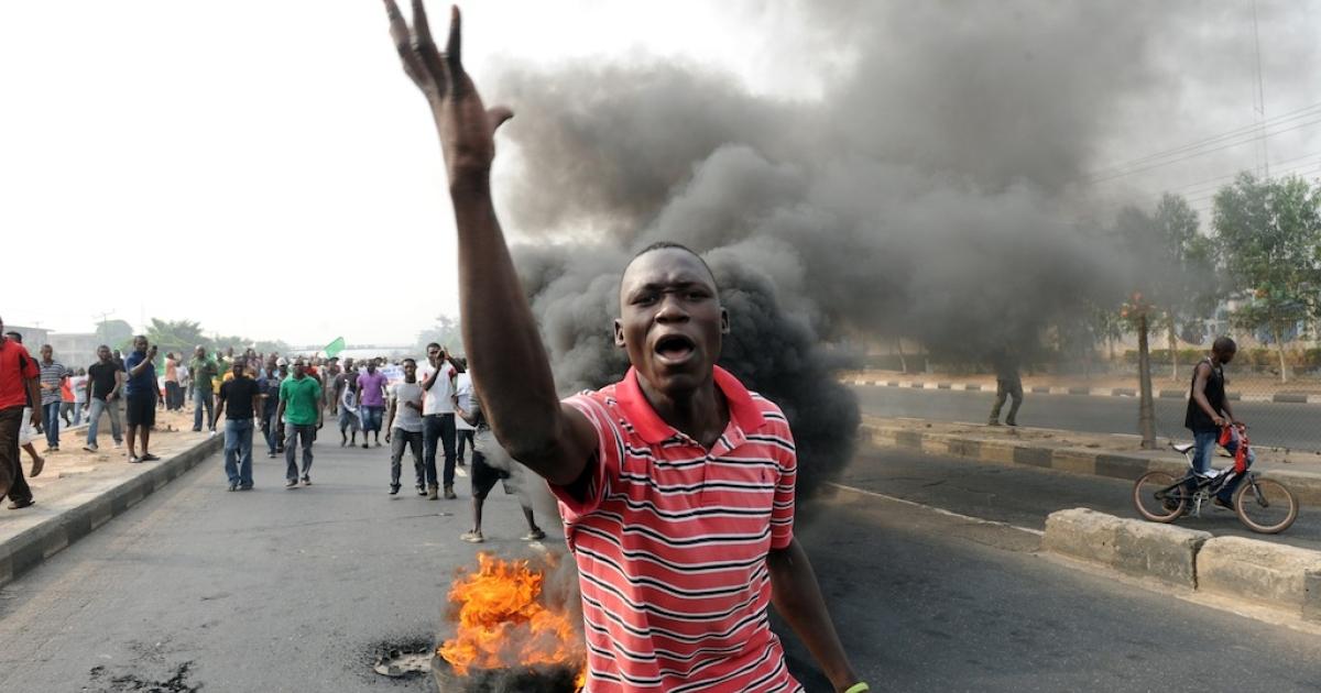 A man gestures in front of a bonfire on Ikorodu Road in Lagos during a protest against soaring petrol prices following government's decision to abolish decades-old fuel subsidies, on January 9, 2012 in Lagos. One protester was shot dead in Nigeria's commercial capital Lagos during the national strike over fuel prices, a union leader said.</p>