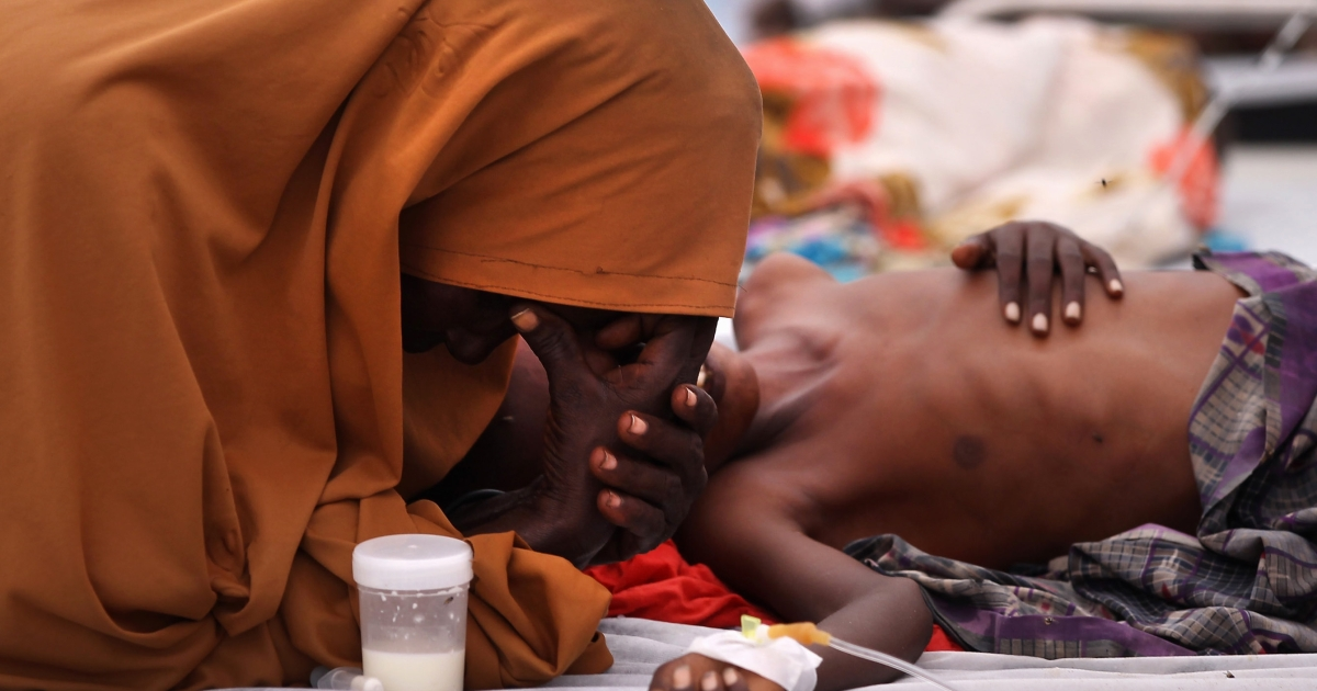 An mother stays by her malnourished son's side in a hospital on August 19, 2011 in Mogadishu, Somalia during a famine that killed as many as 100,000 people.  Aid organizations say thousands lives were lost and millions of dollars were wasted because the international response was too late.</p>