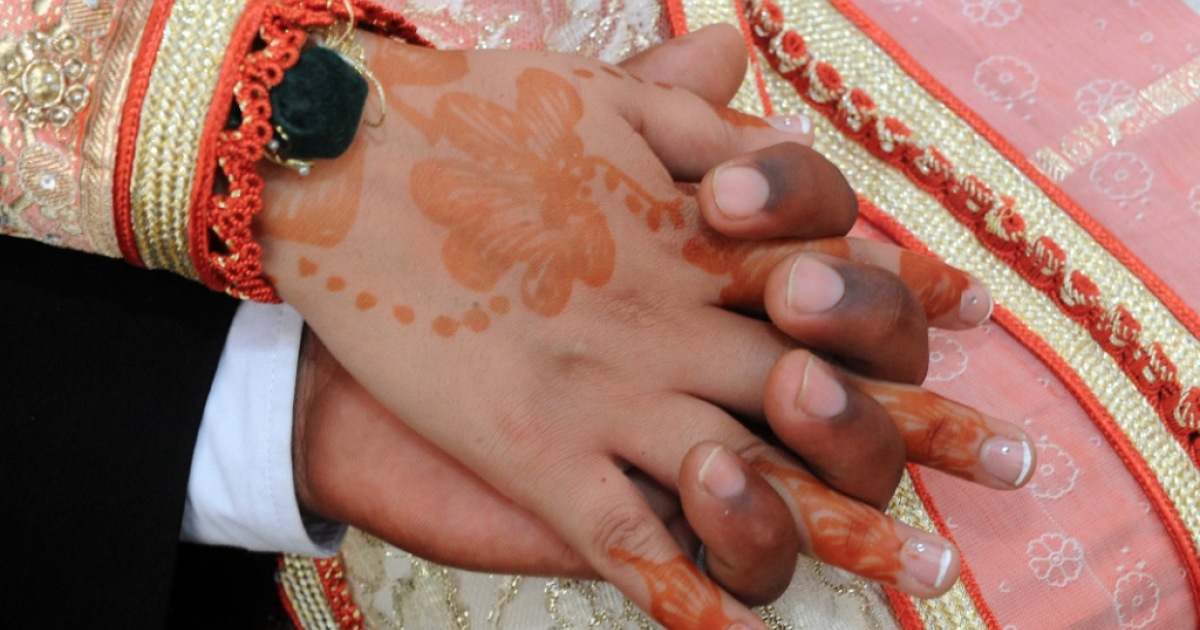 A bride and groom hold hands during a mass wedding ceremony in traditional Moroccan style on July 22, 2010 in Fes. More than one hundred couples married during the event, which was organised by local association Aouraba, and the Council of Fes and financed solely through donations.</p>