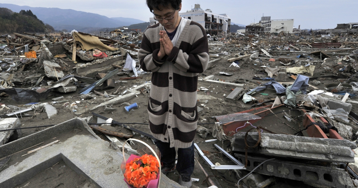 Atsushi Shibata prays for his mother who died in the March 11 tsunami in the devastated town of Rikuzentakata in Iwate prefecture on May 1, 2011.</p>