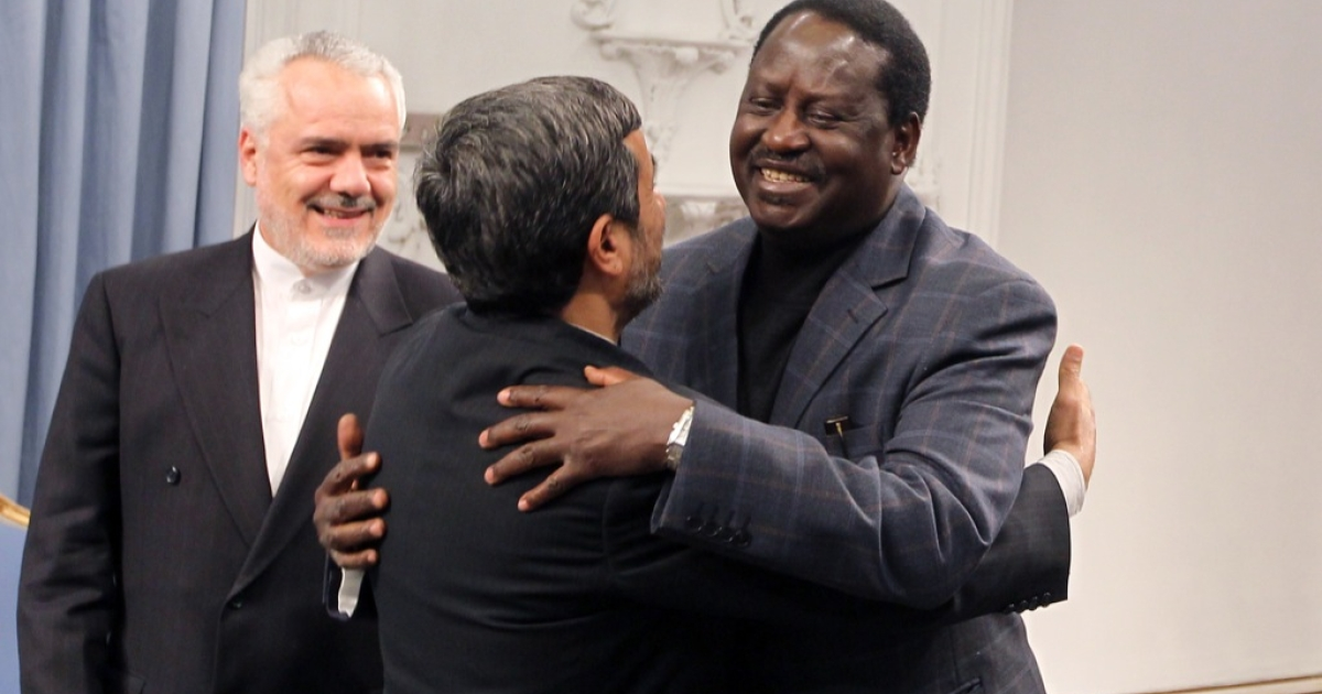 Iran's President Mahmoud Ahmadinejad (C) hugs with Kenyan Prime Minister Raila Odinga (R) as Iran's first vice-president Mohammad Reza Rahimi (L) looks on prior to a meetings in Tehran on March 6, 2011.</p>