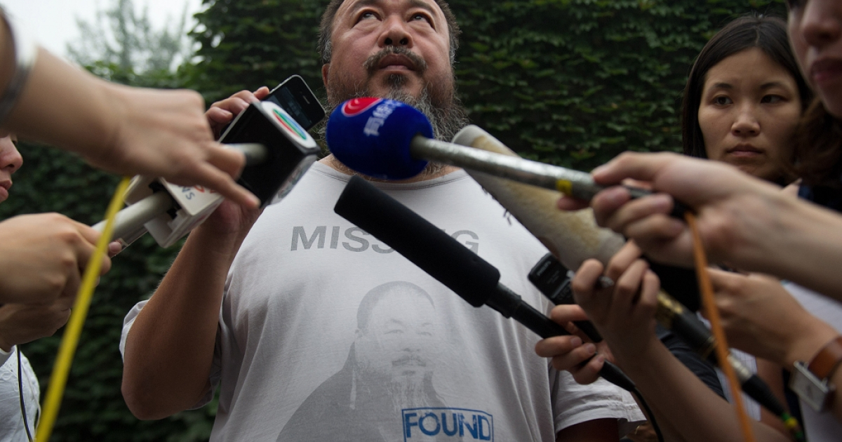 Chinese artist Ai Weiwei (C) speaks to the media inside his compound in Beijing as the verdict of his court hearing is announced on July 20, 2012. Ai Weiwei lost his appeal against a multi-million-dollar tax fine on a company he founded, his lawyer said.</p>