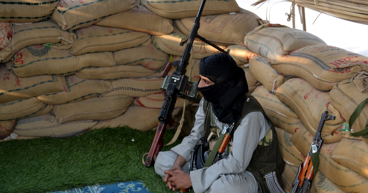 A militant suspected of being a member of Al-Qaeda sits at a checkpoint in Azan in the southern Yemeni province of Shabwa.</p>