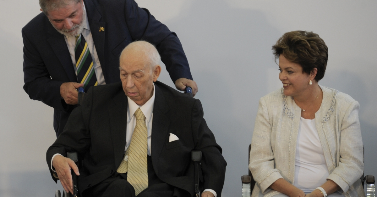 Former Brazilian President Luiz Inacio Lula da Silva adjusts the wheelchair of his former Vice-President Jose Alencar as Brazil's President Dilma Rousseff watches during a ceremony on January 25, 2011.</p>