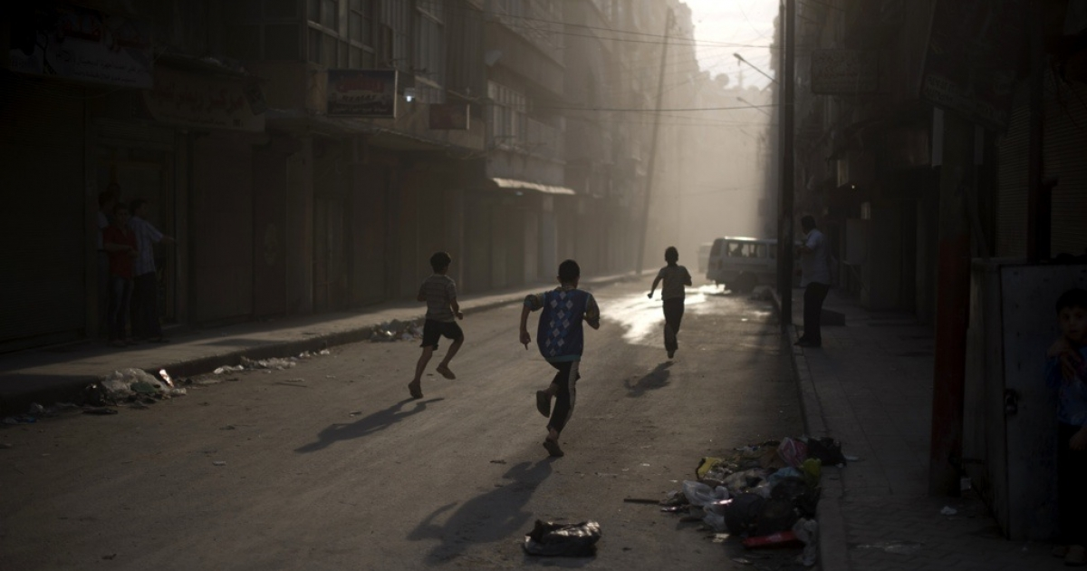 Syrian boys run for cover in Aleppo on Oct. 9, 2012.</p>