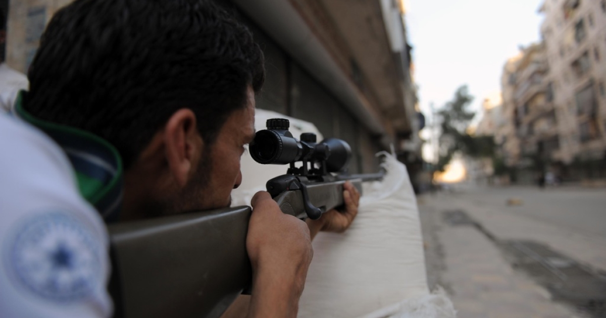 A fighter from the Syrian opposition aims fire during clashes with forces loyal to President Bashar al-Assad, in the center of Syria's restive northern city of Aleppo on July 25, 2012.</p>