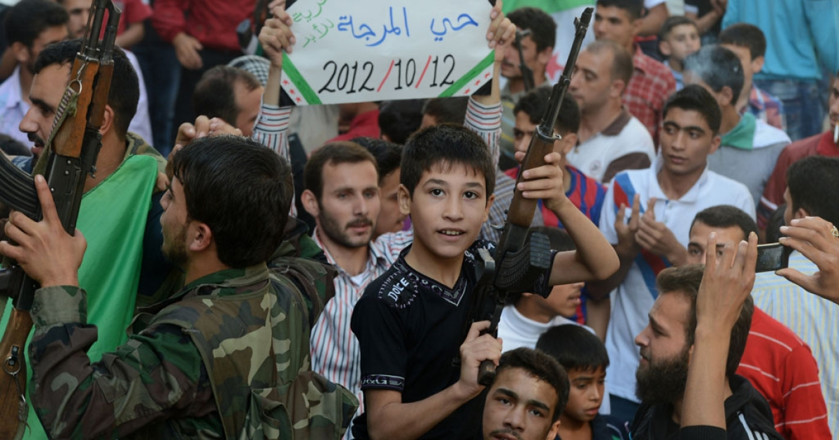 A Syrian boy holds the gun of a Syrian rebel fighter during a protest against the regime of President Bashar al-Assad in the northern city of Aleppo on October 12, 2012.</p>