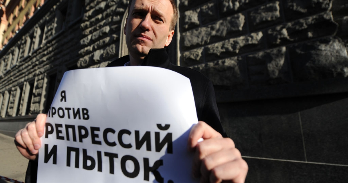Russian opposition activist and blogger Alexei Navalny holds a poster reading