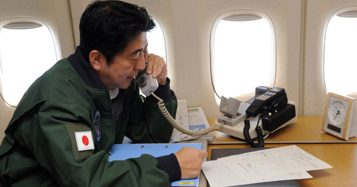 Japanese Prime Minister Shinzo Abe talks on a phone at his office while in flight on a government plane heading to Jakarta from Bangkok on January 18, 2013. Abe is to cut short his visit to Indonesia, to fly home and deal with the hostage crisis in Algeria on January 19 in which numerous Japanese are caught up.  Abe is on the final leg of his first foreign trip since returning to office late last year.</p>