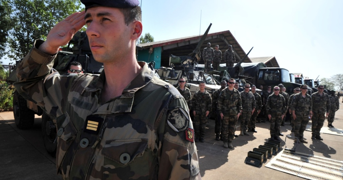 A French army officer stand guard on January 16, 2013 while the Malian president welcomes service at the military airbase in Bamako. France has deployed 700 troops in and around Paris, Interior Minister Manuel Valls revealed Tuesday in the latest indicator of mounting concern over potential reprisals for military intervention in Mali.</p>