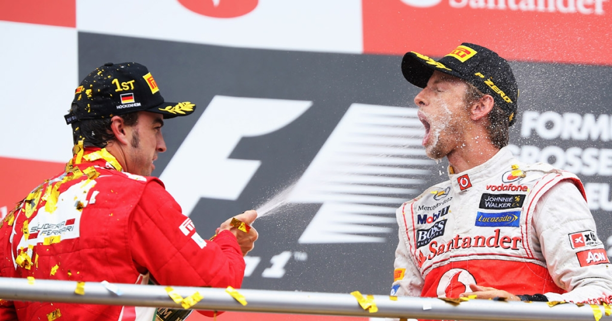 Race winner Fernando Alonso, left, celebrates with third-place finisher Jenson Button of Great Britain on the podium following the German Grand Prix on July 22, 2012, in Hockenheim, Germany.</p>