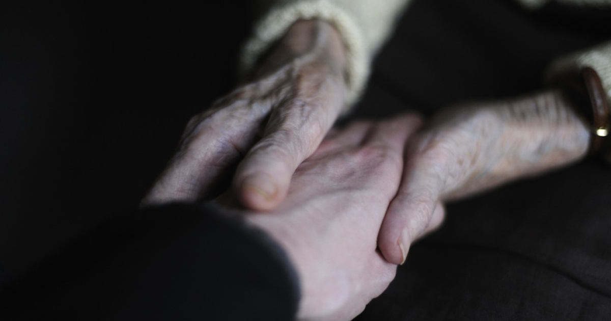 A woman, suffering from Alzheimer's desease, holds the hand of a relative on March 18, 2011 in a retirement house in Angervilliers, eastern France.</p>
