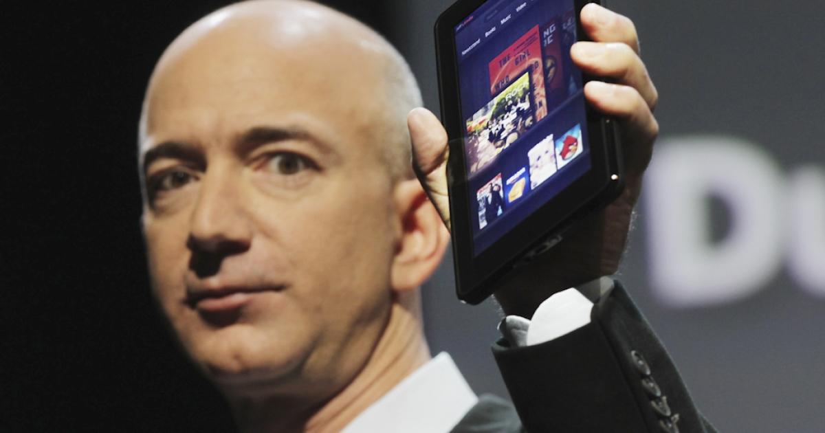 Amazon founder Jeff Bezos holds the new Amazon tablet called the Kindle Fire on September 28, 2011 in New York City. The Fire, which will be priced at $199, is an expanded version of the company's Kindle e-reader that has 8GB of storage and WiFi. The Fire gives users access to streaming video, as well as e-books, apps and music, and has a Web browser. In addition to the Fire, Bezos introduced four new Kindles including a Kindle touch model.</p>