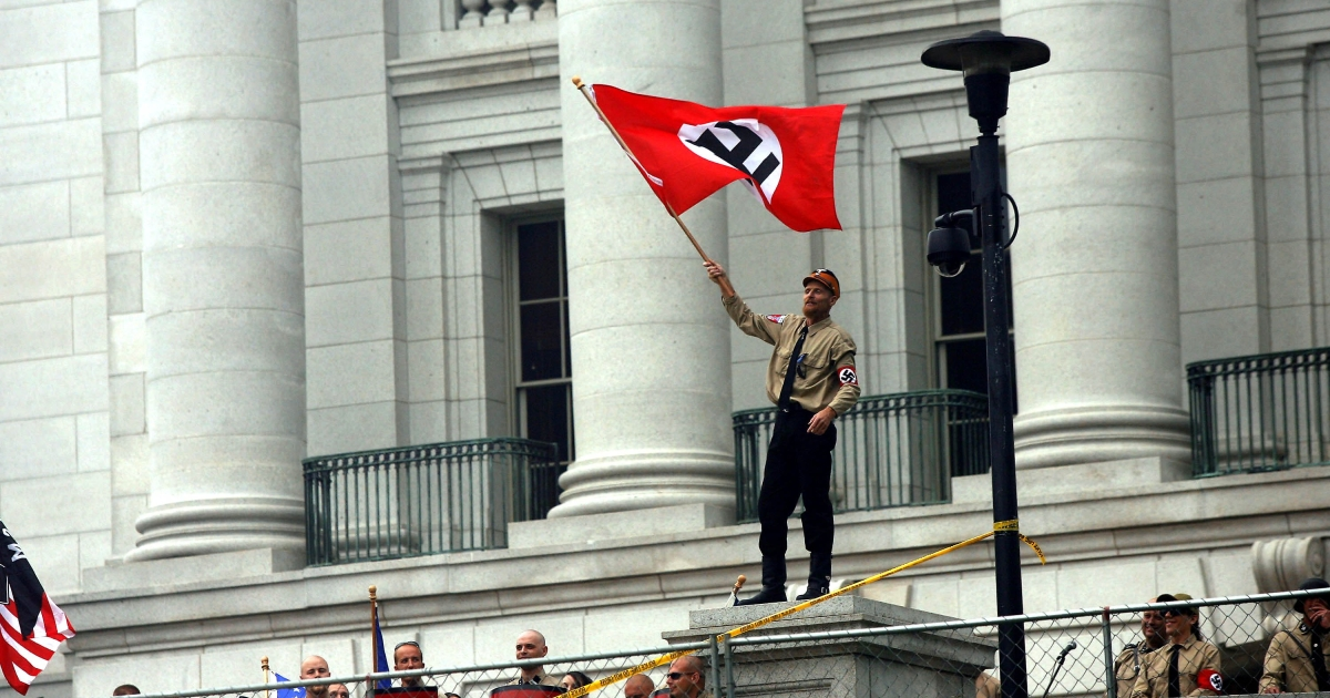 A member of the Minneapolis based National Socialist Movement waves a Nazi flag in Madison, Wisconsin during a rally at  in August, 2006.</p>