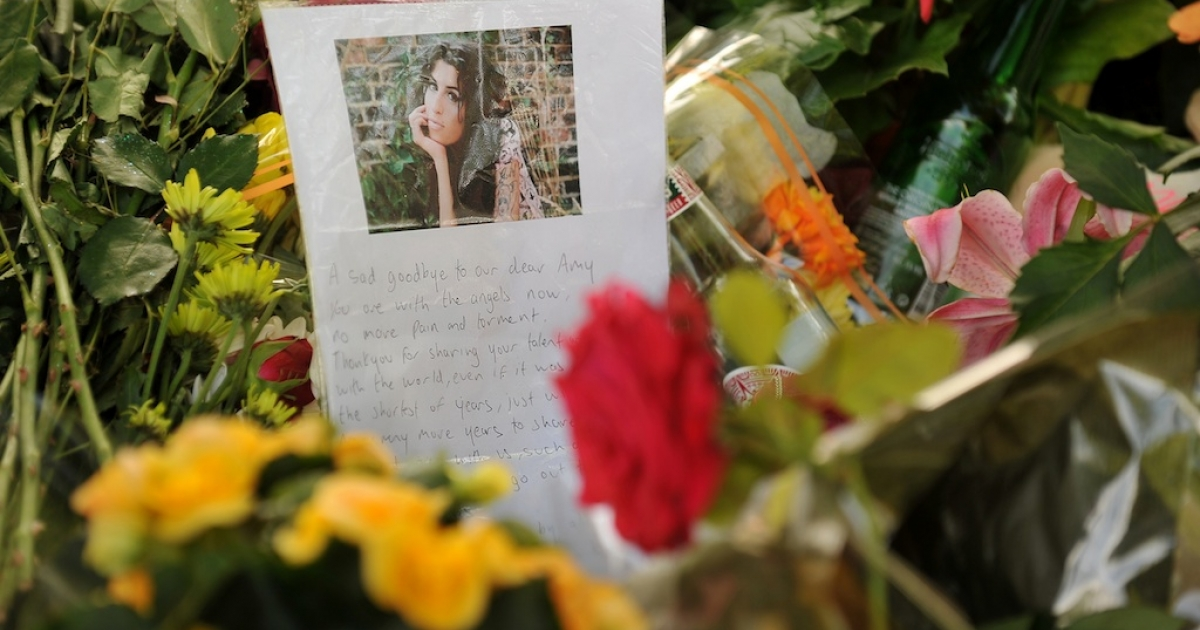 Flowers, pictures and messages are left in tribute to late soul music and British pop star Amy Winehouse, near her home in London, on July 25, 2011.</p>