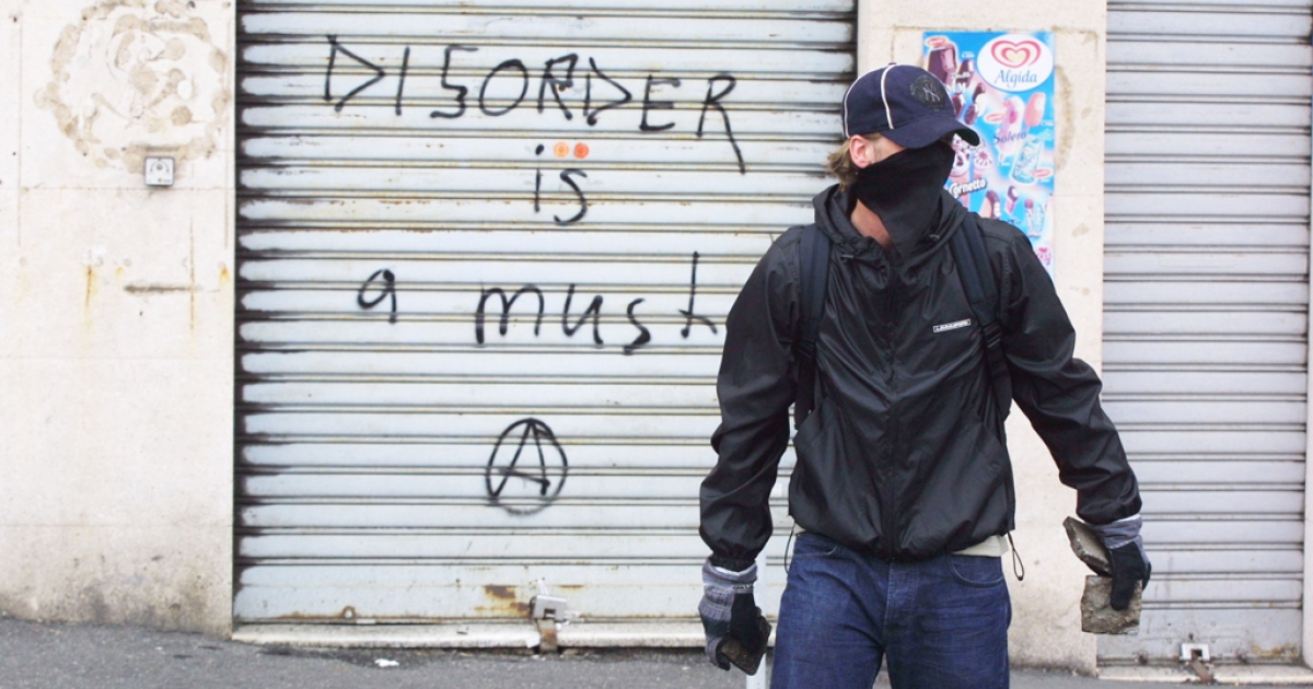 An anti-G8 protester carrying pavement stones passes a graffitied storefront in central Genoa. Officials suspect Genoa's anarchists may have been responsible for the shooting of the CEO of a nuclear firm.</p>