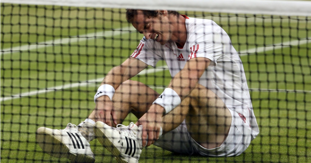 Andy Murray of Great Britain grimaces after falling during the men's final against Roger Federer at Wimbledon on July 8, 2012, in London, England.</p>