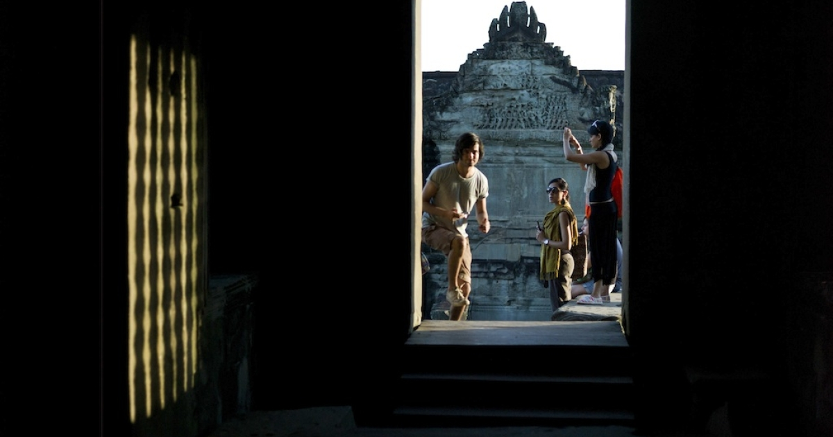 Tourists visit the world heritage Angkor Wat temple during sunrise in Siem Reap province, some 300 kilometers northwest of Phnom Penh on July 14, 2012. Built by King Suryavarman II in the 12th century, Angkor Wat is considered the largest Khmer temple complex in the world.</p>