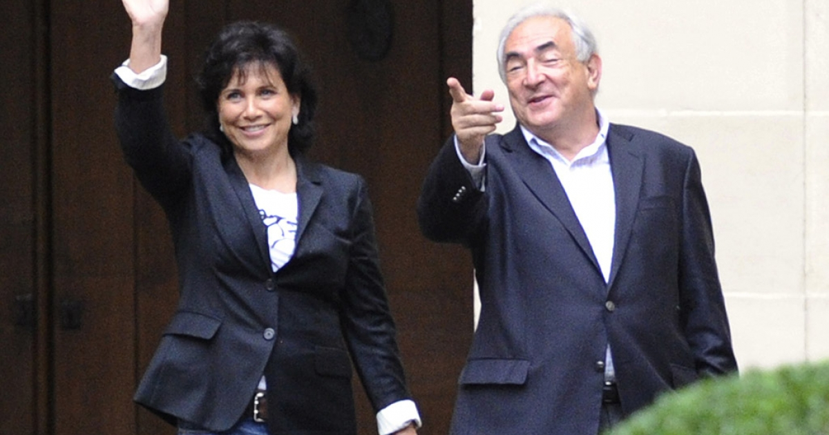 Former IMF leader Dominique Strauss-Kahn and his wife Anne Sinclair wave from the courtyard upon their arrival in their Paris home. Sinclair was voted Woman of the Year in an online magazine's poll.</p>