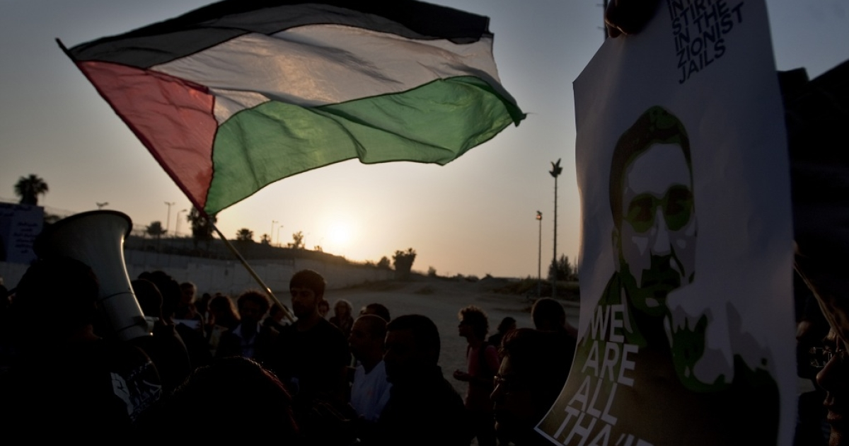 Palestinian and Arab Israeli protestors wave the Palestinian flag and hold a poster picturing Thaer Halahla, who has been on hunger strike for more than 64 days, during a demonstration in solidarity with Palestinian prisoners held in Israeli jails outside the Massiyahu Prison in Ramle, near Tel Aviv, on May 3, 2012 At least 1,550 imprisoned Palestinians are now taking part in a mass hunger strike, Israel's Prison Service said on May 2.</p>