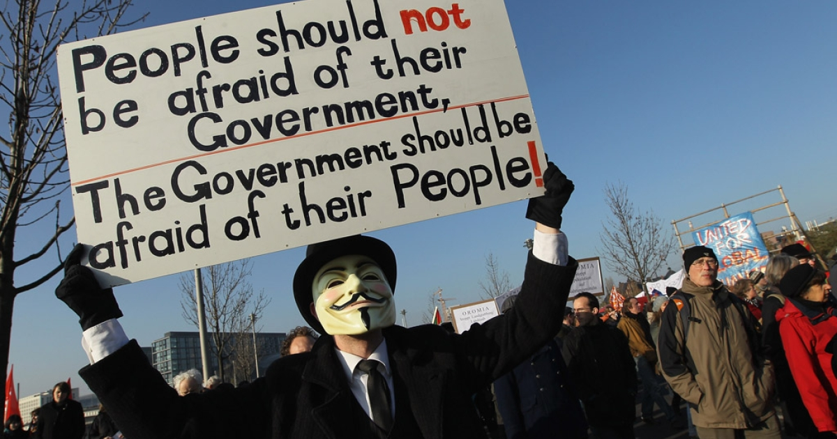 A man wearing an Anonymous mask joins demonstors protesting against the world financial system. Anonymous has shut down the Department of Justice website, among others, in protest of the recent shutdown of file sharing site Megaupload.</p>