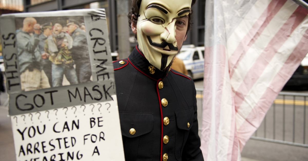 A young man with an Anonymous mask, wearing a military uniform, marches with Occupy Wall Street protesters on November 11, 2011 at Zuccotti Park in New York. Anonymous' latest target is New York-based police supplier Iron Works.</p>