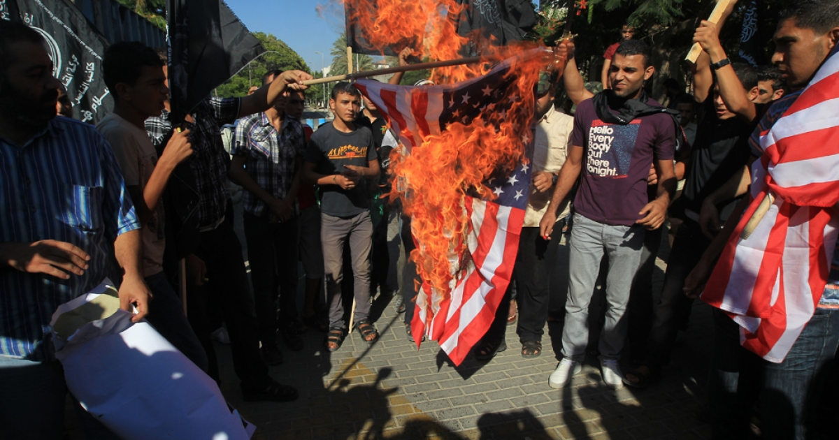 Palestinian men burn the US flag during a demonstration against a film deemed offensive to Islam, on September 12, 2012  in front of the United Nations headquarters in Gaza City.  A film at the center of anti-US protests in the Middle East which killed a diplomat was made by an Israeli-American who describes Islam as a