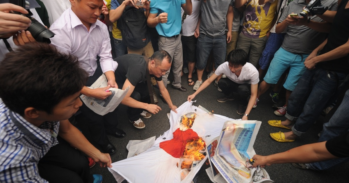 Anti-Japan protesters burn a Japanese national flag during a protest over the Diaoyu islands issue, known as the Senkaku islands in Japan, in the southern Chinese city of Shenzhen on September 18, 2012. Thousands of anti-Japan protesters rallied across China over a territorial row on a key historical anniversary, as Japanese firms including car giant Toyota shut or scaled back production in across the country.</p>