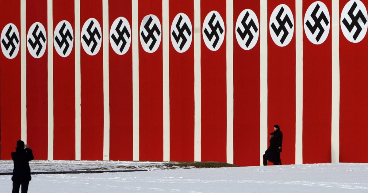People walk in front of a big wall draped with flags with Nazi symbols in Berlin's Lustgarten in front of the Old Museum. A new study has found that 20 percent of Germans still harbor latent anti-Semitism.</p>
